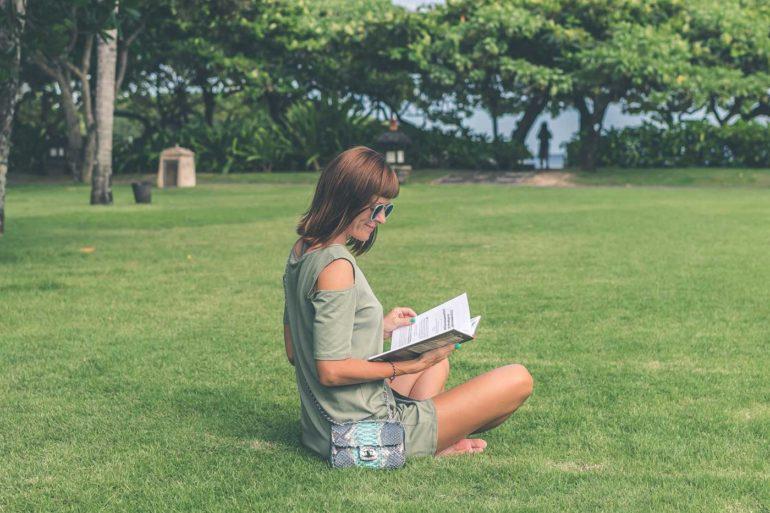 Kobieta siedzi na tawie i uśmiecha się czytając książkę