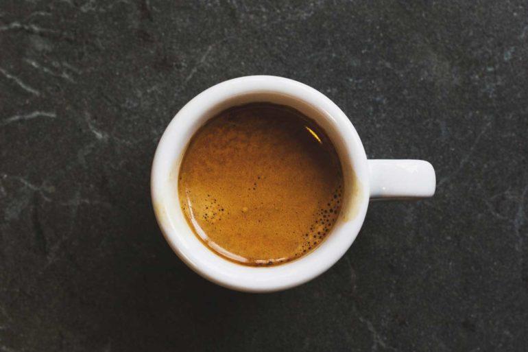 biały kubek z kawą postawiony na czarnym blacie