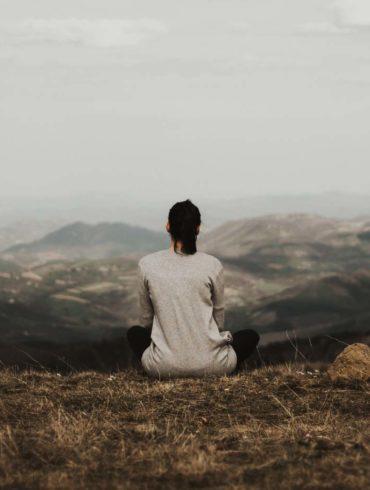 kobieta siedzi na trawie i rozkoszuje się widokiem gór