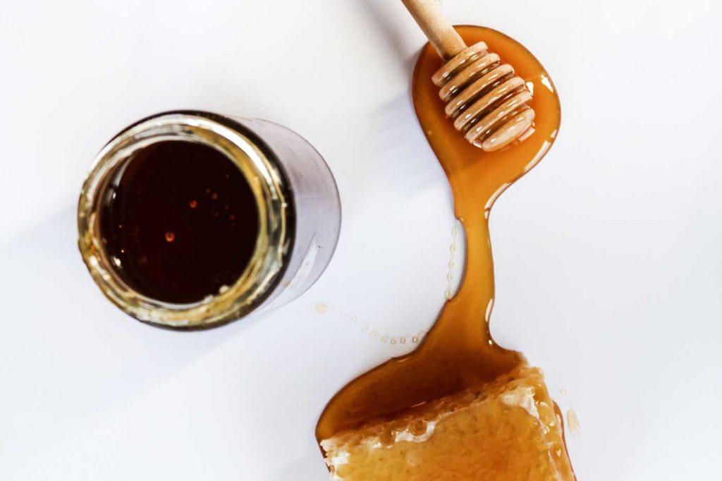 słoik miodu, drewniana pałeczka do miodu i kawałek plastra miodu