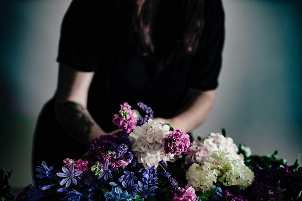 Pani z tatuażem na ręce komponuje bukiet z kwiatów