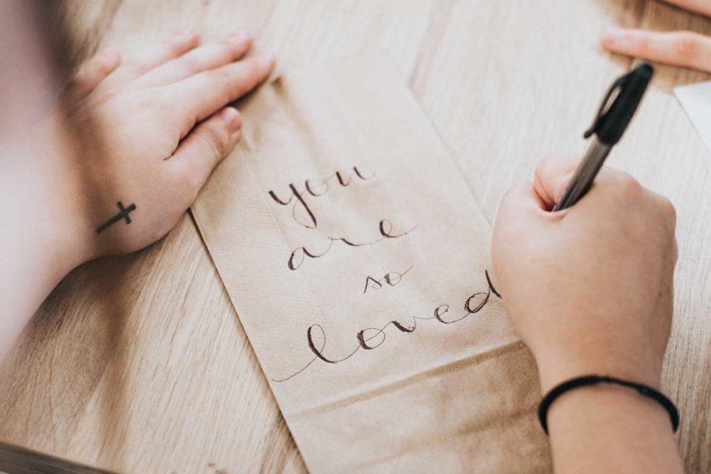 kobieta starannie i estetycznie pisząca napis you are so loved
