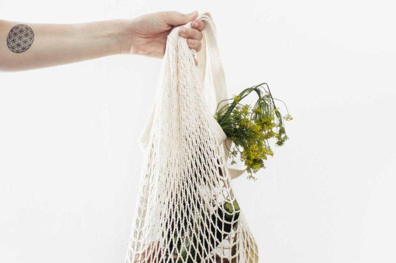 Kobieca ręka trzyma ekologiczną siatkę ze sznurka wypełnioną warzywami