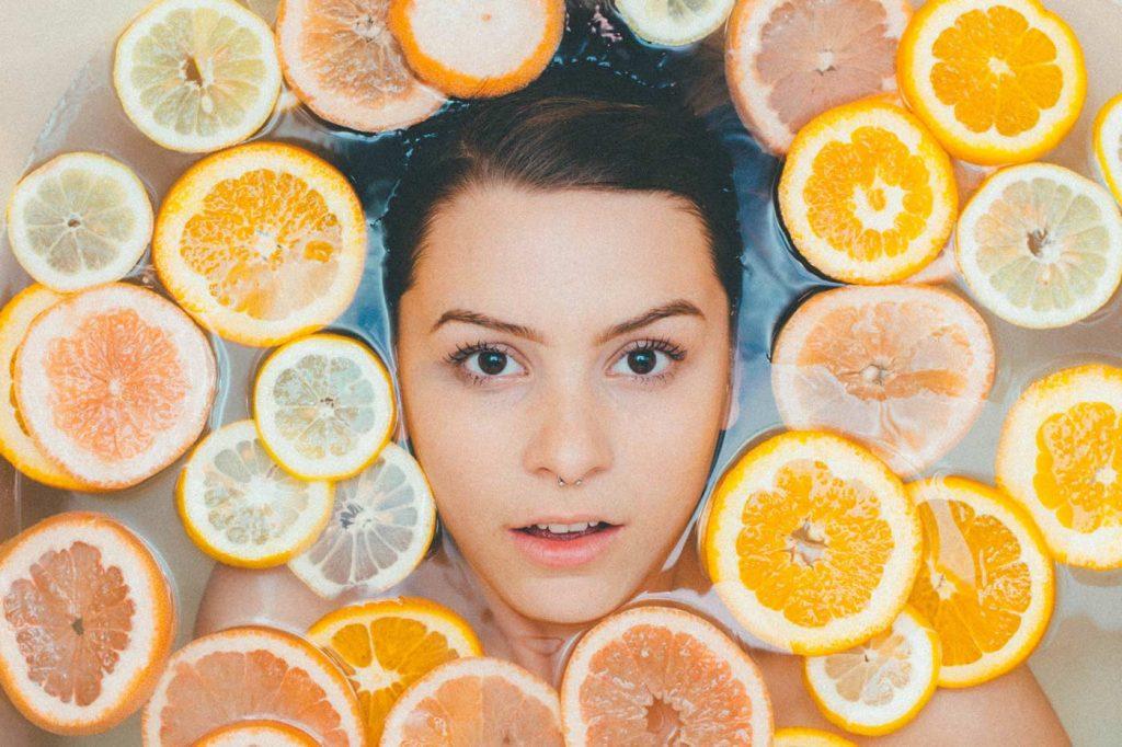 Kobieta w kąpiel z plastrami pomarańczy i grejpfrutów