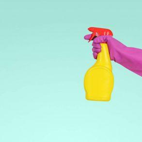Ręka w różowej rękawiczce trzyma żółtą butelkę z płynem do czyszczenia