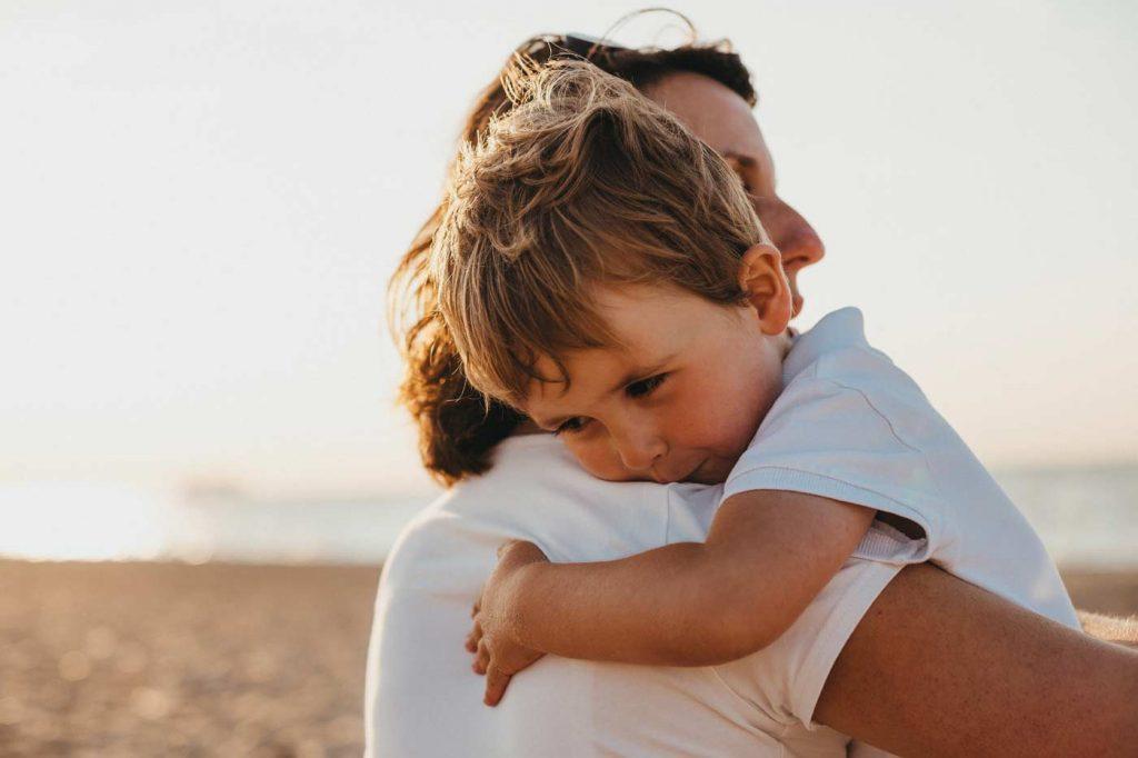 Kobieta na plaży przytula swoje dziecko