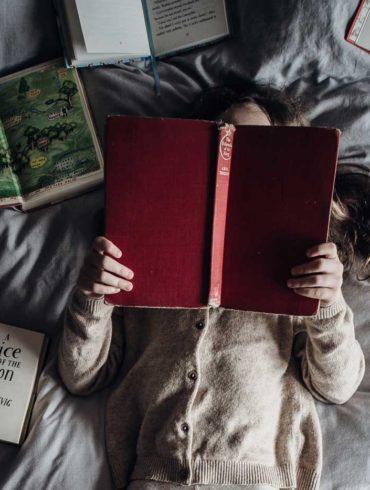 Kobieta leży na łóżku i czyta książkę.
