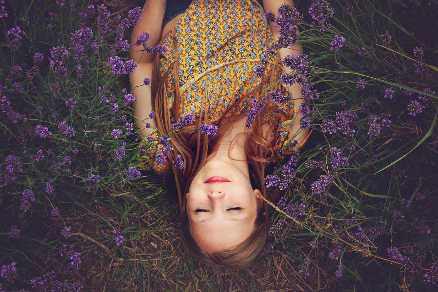 Kobieta leżąca na łące wśród kwiatów