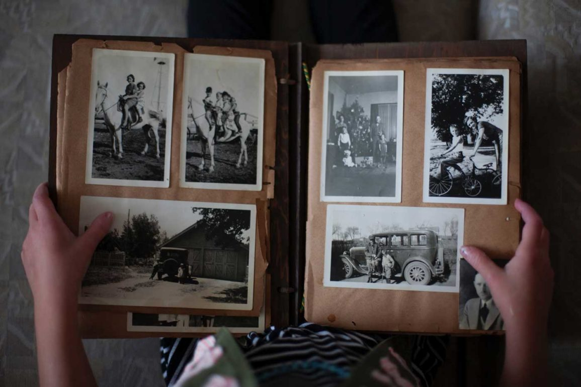 osoba oglądająca album ze starymi zdjęciami