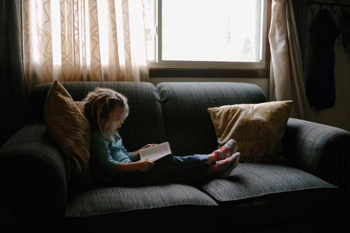 Dziecko siedzące wygodnie na sofie i czytające książkę.