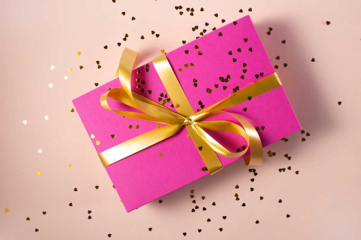 prezent zapakowany w różowy papier i złotą wstążkę.