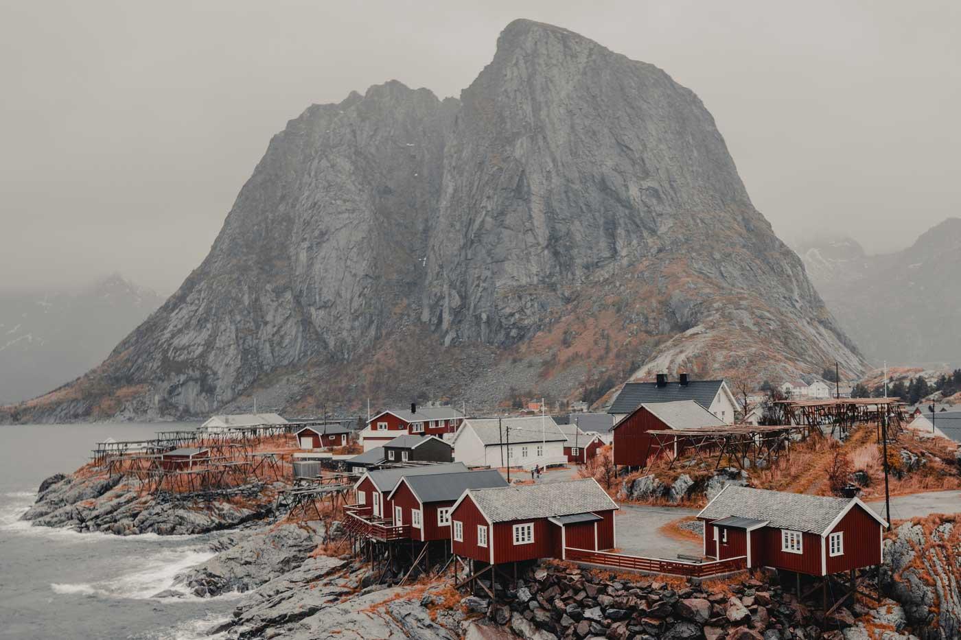 Lofoty w Norwegii. Czerwone domki przy wodzie na tle ogromnej góry