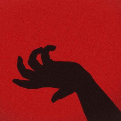 cień ręki na czerwonym tle