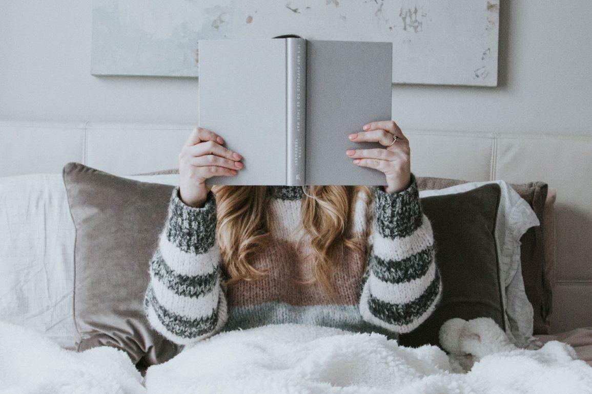 Kobieta w łóżku czyta książkę