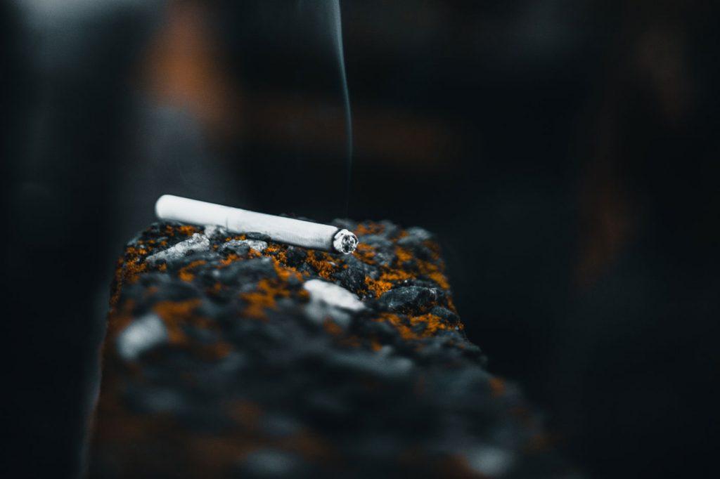 Dymiący się papieros leży na murku