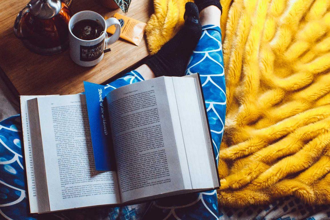 kobieta w pidżamie czyta książkę.