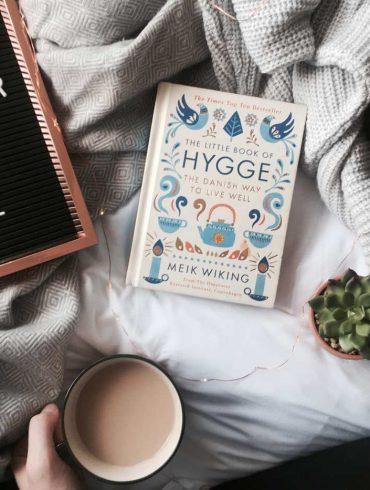 Książka hygge klucz do szczęscia na łóżku