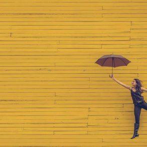Kobieta trzymajaca parasolkę unosi się na ziemią.