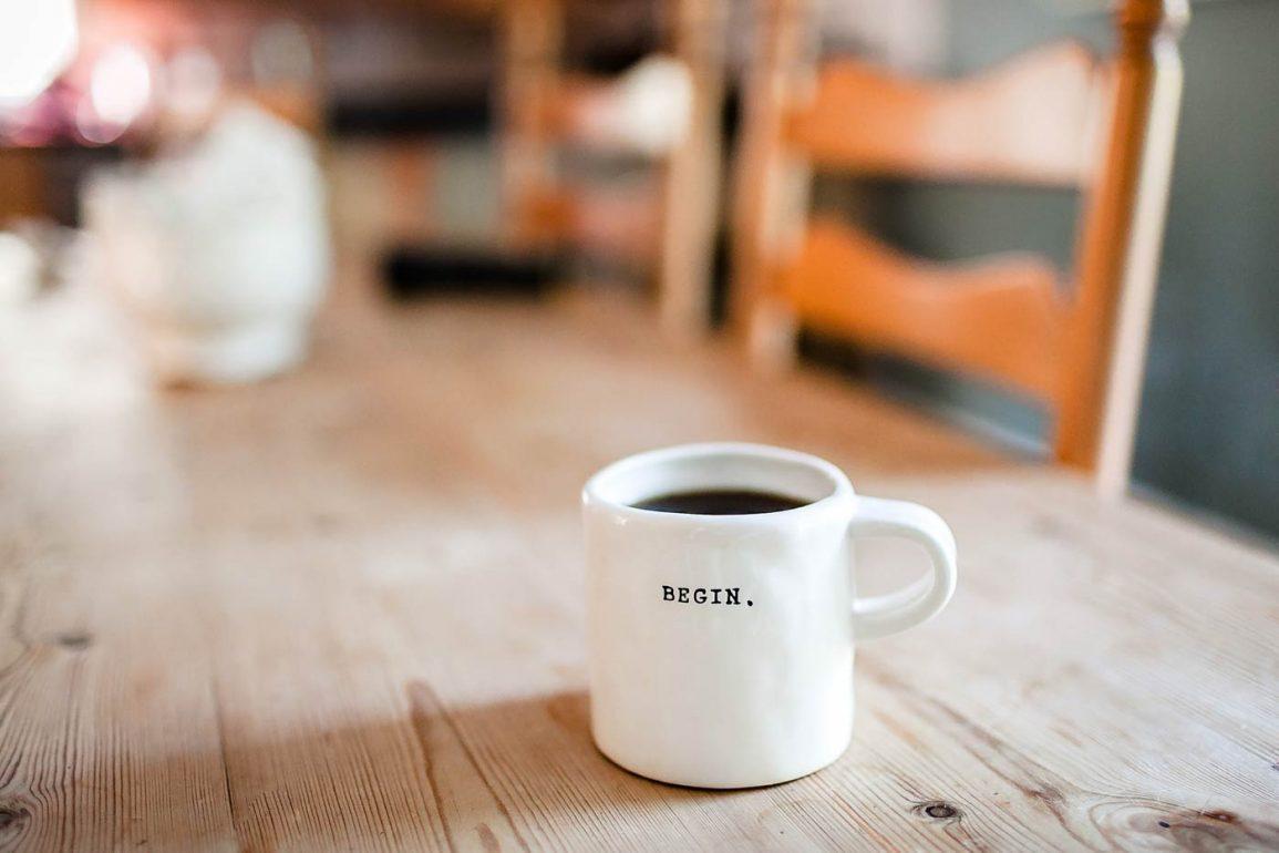 """Biały kubek wypełniony kawą z napisem """"begin"""""""