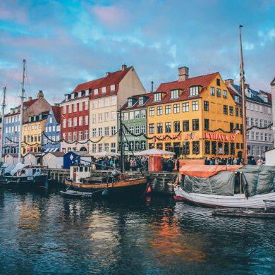 Ulica z jaskrawo kolorowymi kamieniczkami i i kanał Nyhavn w Kopenhadze.