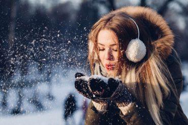 kobieta zdmuchuje śnieg ze swoich dłoni