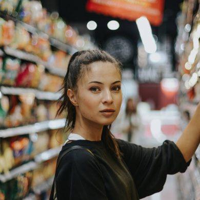 Młoda kobieta sięga po produkt umieszczony na sklepowym regale